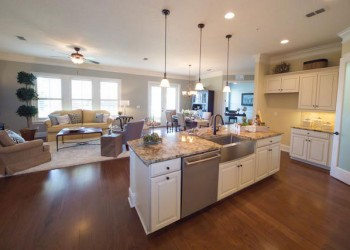 Wide angle of a living room looking into a kitchen and dining room