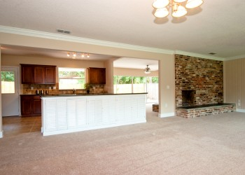Wide angle of a living room looking into a kitchen