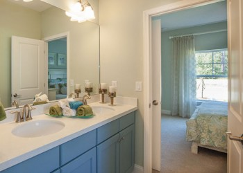 Wide angle of a bathroom looking into a bedroom