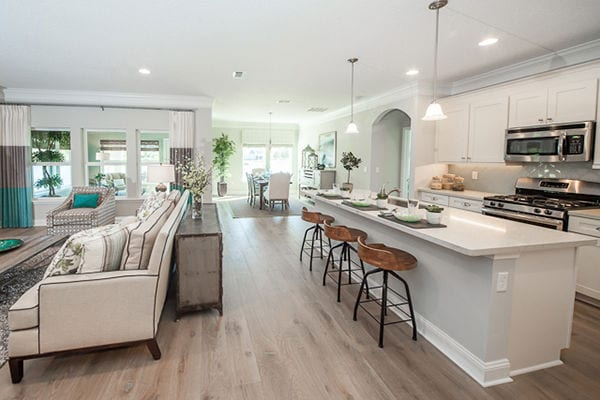 Wide angle of a kitchen looking into the dining and living area